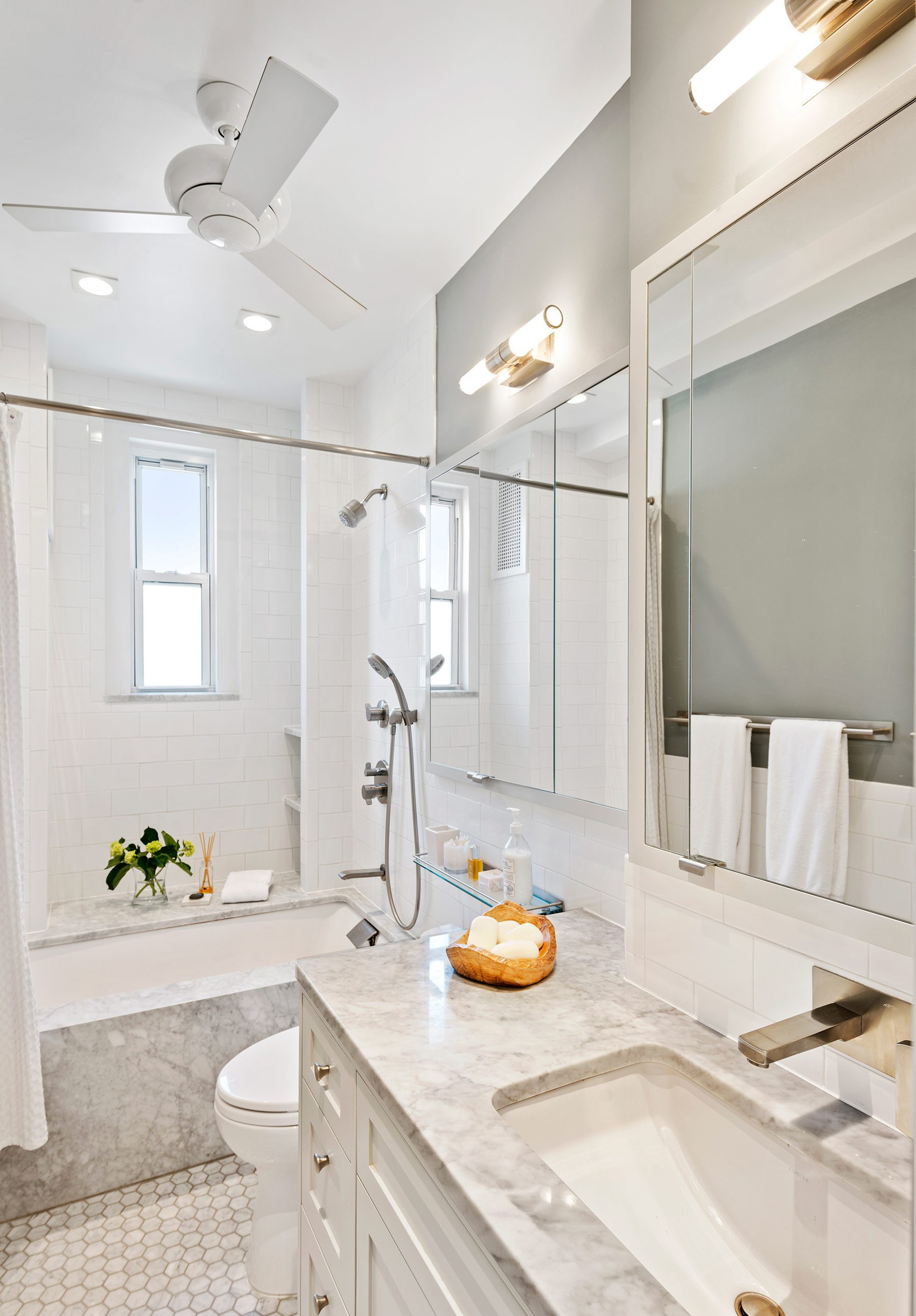 white and marble bathroom with tub, shower and ceiling fan
