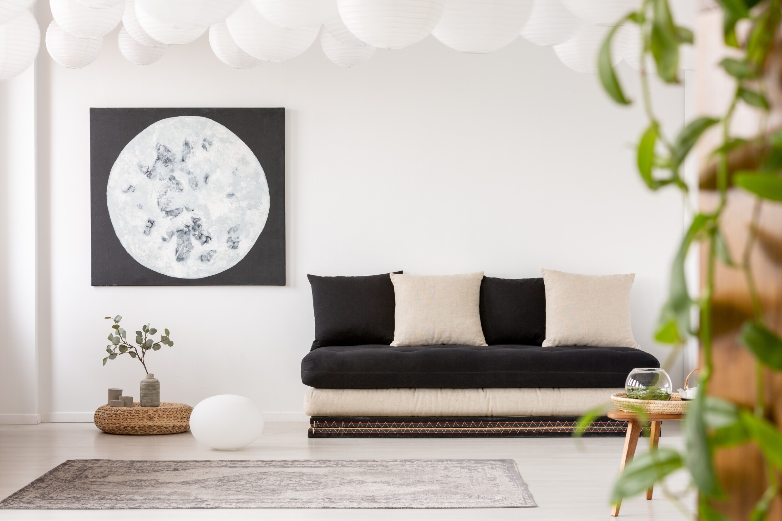 Pillows on black sofa in white living room interior with moon poster and grey carpet