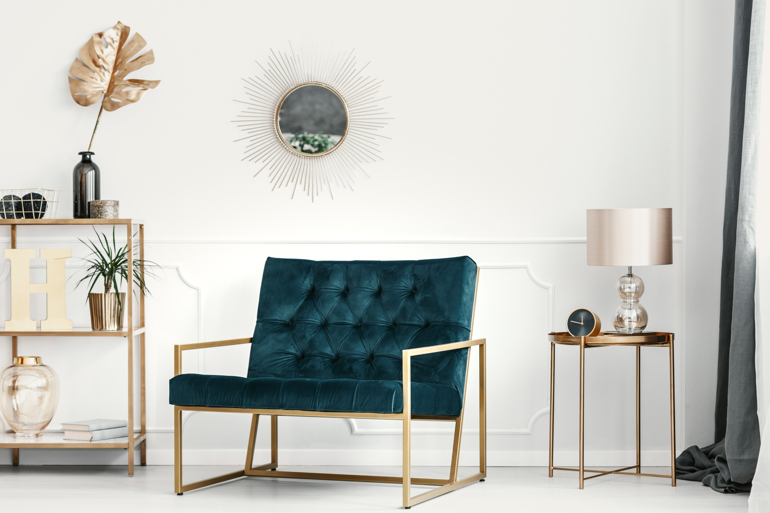 emerald green sofa by a white wall with molding